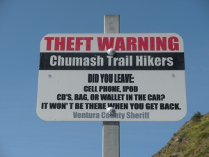 Theft Warning Sign posted at a trailhead located just off Pacific Coast Highway in the Santa Monica Mountains National Recreation Area.